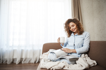 Woman decided to treat herself in bright good day. Portrait of attractive female curly-haired female sitting on sofa in pyjamas, drinking coffee, enjoying reading magazine, covering feet with blanket Stock Photo