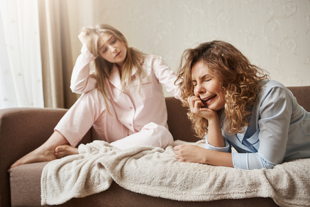 Girl crying her heart out of being lonely without couple. Beautiful european blonde in nightwear sitting on sofa, patting sad miserable girlfriend with curly hair, trying to calm her down and cheer up