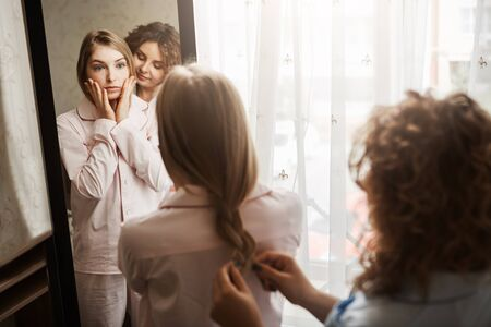 Girl is worried about appearance, having tired face in morning after waking up. Two beautiful caucasian women standing near mirror. Blonde daughter in nightwear waiting while friend making hairstyle Stock Photo