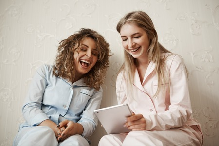 Let me show you funny video. Portrait of beautiful caucasian blond sister in nightwear spending leisure with friend, holding digital tablet while reading hilarious joke or article, having fun together Stok Fotoğraf