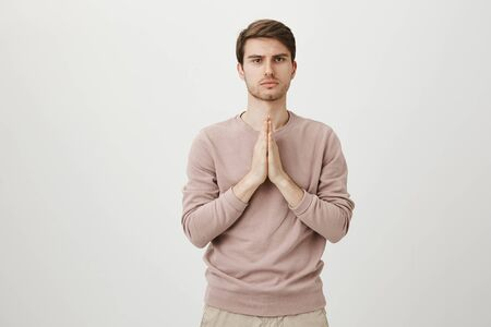Young and attractive man with bristle standing with praying or begging gesture while expressing confidence and being calm, over gray background. Yoga trainer greets his group before starting exercise