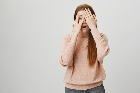 Attractive european redhead woman covering eyes with hands and peeking through it, being curious what will happen, standing over gray background. Girl is scared of horror but also very interested.
