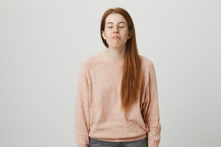 Funny and childish cute redhead caucasian female trying to reach her nose with tongue while looking at it and smiling, standing over gray background. Girl tries to convince friends she can make it