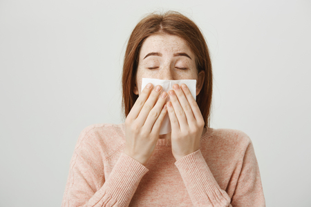 Close-up portrait of cute redhead european woman with freckles sneezing or blowing out nose in napkin while standing with closed eyes over gray background. Girl suffers from allergy or cold symptoms