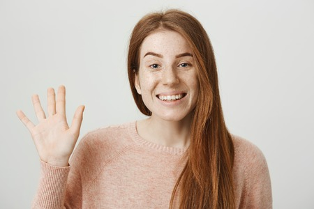 Close-up portrait of cute ginger girl waving with hand and smiling broadly at camera while standing over gray background. Singer met her mates from band and ready to practice.