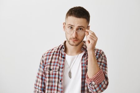 You really mean what you said. Surprised or questioned attractive student taking off trendy glasses and looking at camera as if being stunned with sudden question or revelation over gray wall