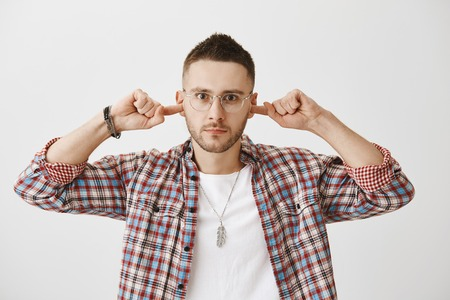 Enough of your excuses, I am done with you. Portrait of angry or annoyed young man with beard, wearing trendy glasses and plaid shirt, covering ears with index fingers and looking angry at camera
