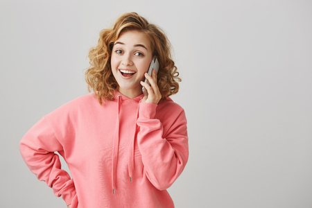 Hello it is me. Portrait of happy good-looking curly haired blonde female talking on smartphone, surprised to receive phone call, saying hi with broad smile while standing over gray background 版權商用圖片