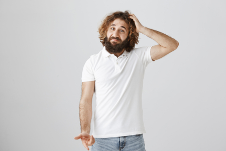 Man in not sure he bought what wife asked. Portrait of uncertain questioned eastern guy with curly hair scratching head and gesturing, lifting eyebrows with confused expression over gray wall