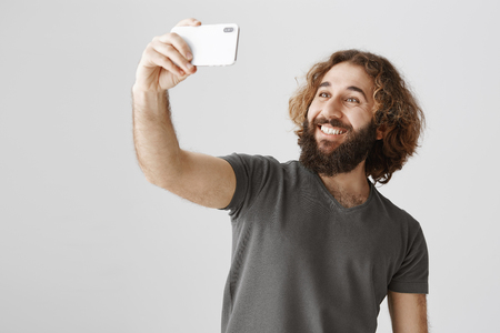 Handsome easter bearded man on vacation taking selfie to show his friends where he is travelling, holding smartphone and smiling at screen tilting body behind to fit in photo, standing over gray wall
