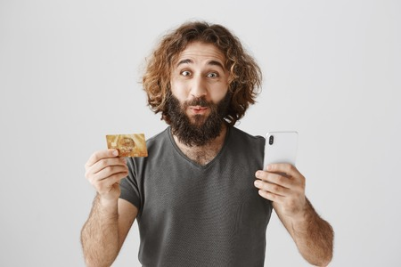 Customer amazed with fast feedback. Portrait of surprised excited eastern guy with curly hair and beard showing credit card and smartphone, using new online banking function, satisfied with result