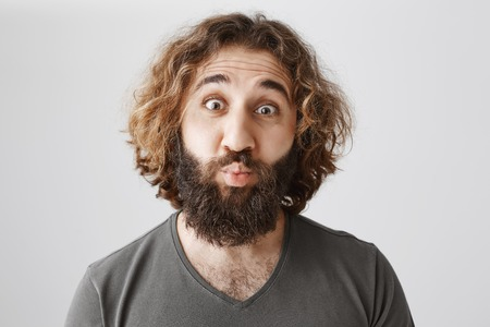 Small kiss for charming husband. Portrait of funny emotive eastern guy with curly hair and beard folding lips in mwah, lifting eyebrows, being surprised seeing rejection, standing over gray wall