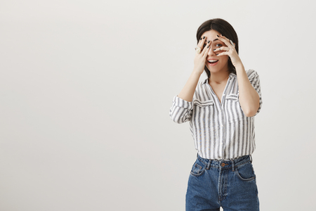 I see you peeping through fingers. Studio shot of gorgeous stylish caucasian woman with short dark hair being in excited mood, covering eyes with hands, being curious what is happening over gray wall Stock Photo