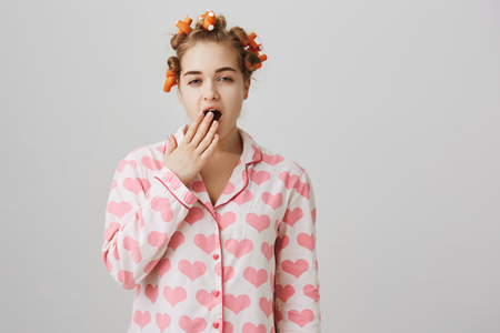 Am I already pretty. Portrait of funny cute caucasian girl at home, wearing hair curlers, trying to create beautiful hairstyle, yawning, being sleepy while standing in pyjamas over gray background Foto de archivo