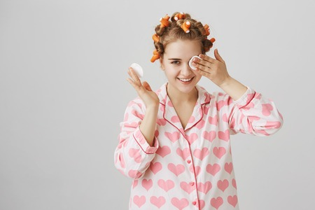 Maybe I do not see but hear. Portrait of cute funny european female in hair curlers and nightwear wiping off mascara with cotton pads, getting ready to sleep while standing over gray background