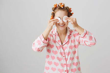 Girl looks like alien while wiping off mascara. Portrait of funny emotive woman in hair curlers and pyjamas with heart print holding cotton pads on eyes and smiling, having fun with friend