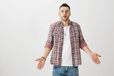 Shocked and confused caucasian male model in glasses and trendy outfit standing with spread palms and opened mouth, being stunned and caught off guard. Guy did not understood when he was robbed
