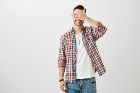 Optimistic male with bristly in checked shirt over t-shirt smiling brightly while covering eyes with palm, being confident and calm over gray background. Guy trust his girlfriend so he follows her Archivio Fotografico