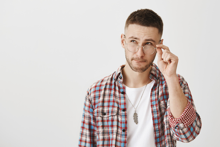 Guy trying to make calculations in mind. Indoor shot of good-looking modern male with beard, wearing and holding eyewear while looking up with thoughtful expression, making decision over gray wall