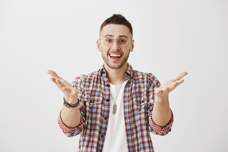 My friend I am glad to see you. Young attractive sportsman with stylish haircut in glasses pulling hands towards camera and directing at someone while being happy and excited, cheering best friend Stock fotó