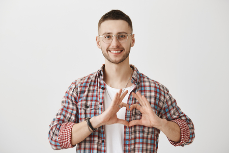 Happy to be in love with you. Studio shot of good-looking ordinary guy in glasses showing heart sign over chest, smiling cheerfully, making video confession for his girlfriend who is now abroad