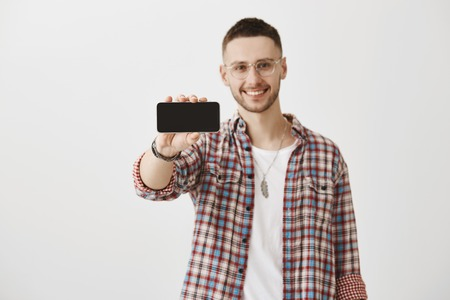 Eager to buy new gadgets. Studio shot of attractive macho model in glasses pulling hand with smartphone towards camera while presenting it, smiling broadly and standing over gray background.