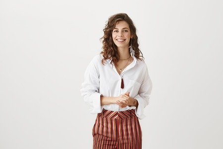 She guarantees good service. Attractive slender woman in trendy striped pants standing over gray background with cheerful smile and holding hands together over chest, trying to control herself