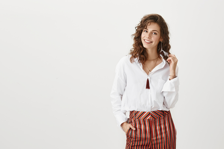 Confident girl on party with her girlfriends. Good-looking caucasian female in trendy blouse and striped trousers, touching feather-earring and smiling sensually while looking at camera.