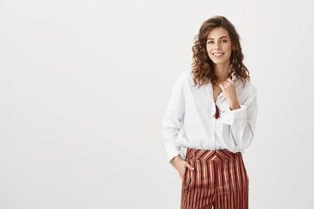 Simple outfit speaks loudest. Portrait of emotive charming adult woman with trendy hairstyle and fancy striped pants, holding fist near chest and smiling broadly, feeling carefree over gray background