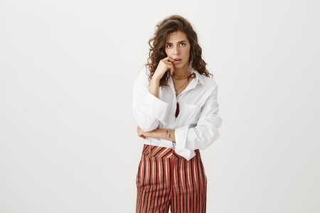 Worried and thrilled caucasian businesswoman in stylish outfit and with curly hairstyle biting finger while looking troubled and intrigued at camera over gray background. Woman hears terrifying gossip