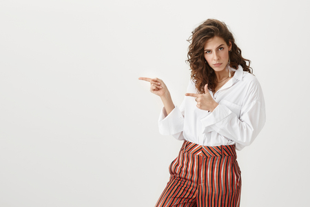 Best copy space for you. Portrait of attractive funny woman with curly hair, wearing trendy outfit and indicating left with index fingers, looking serious and convincing customer to buy her product