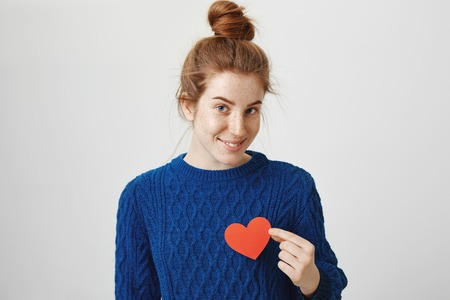 Heart beats faster when I see you. Portrait of attractive sensual redhead female with freckles holding paper heart near chest and looking with cute smile at camera, being shy while confessing in love