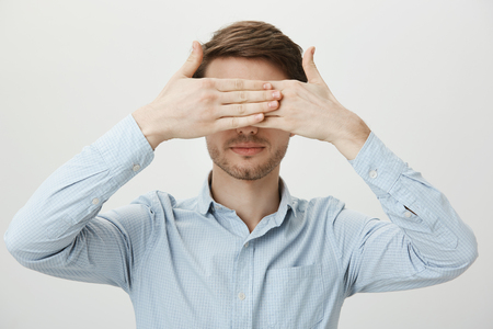 Did not see so did not happen. Portrait of calm relaxed young man with bristle covering eyes with both palms, standing in ordinary blue shirt against gray background without any emotions
