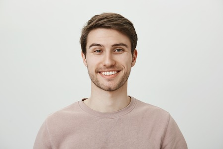 Confident attractive caucasian guy in beige pullover smiling broadly while standing against gray background, feeling self-assured while helping out customer, giving some advice about his investments Stock Photo