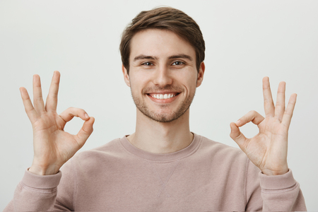 Everything is awesome. Portrait of satisfied good-looking mature caucasian guy with bristle showing okay or fine gesture with both hands, telling that he feels great and all work is done.