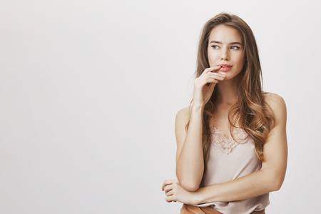 Charming woman has sharm mind and great ideas. Portrait of intrigued thoughtful feminine female model touching lips, looking aside while thinking and making up plan, standing over gray background Stock Photo