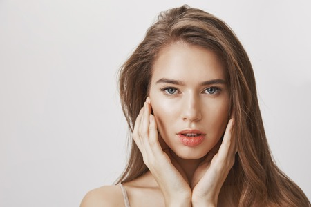 Studio shot of romantic attractive woman with natural makeup gently touching face and gazing at camera with focused confident expression, feeling relaxed and self-assured of her beauty over gray wall