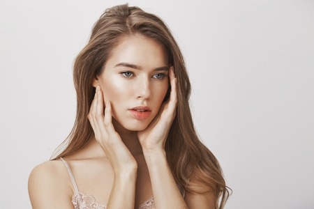Indoor shot of attractive confident european female model touching face gently, looking aside and being in dreamy and relaxed mood, posing for skincare or makeup advertisement over gray background