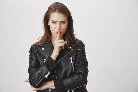 Shh, listen to me. Attractive beautiful european woman holding index finger over mouth, looking sensually at camera, saying shush, asking boyfriend to keep secret or stay silent over gray wall