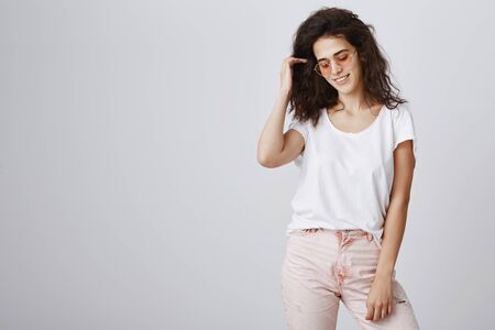 Living fashionable and modern life. Portrait of stylish urban curly-haired woman in trendy sunglasses and pink trousers looking down and smiling broadly while posing during advertising campaign Stock Photo