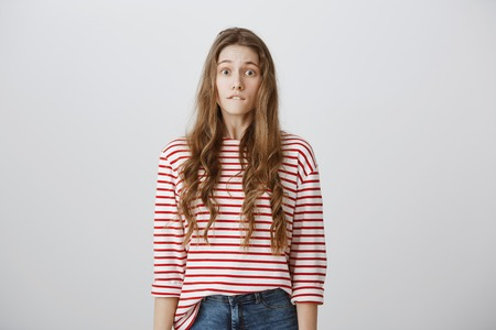 Oops, what have I done. Studio shot of worried beautiful young girl with blonde hair in striped shirt biting lower lip, feeling guilty and ashamed, anxious of someone knowing truth over gray wall