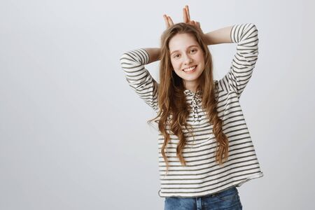 Studio shot of positive happy caucasian teenage female holding hands behind head, mimicking horns, tilting and smiling broadly, expressing friendliness, being cute over gray background Standard-Bild