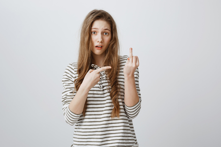 Annoyed girl suggests to fuck off. Portrait of cool bothered young woman showing middle finger and pointing at rude gesture with forefinger, being angry and irritated during fight or quarrel