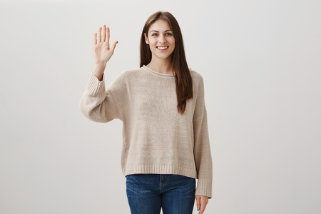Girl waves her friend so she can find her in crowd. Studio shot of positive charming woman in casual clothes standing with raised palm and smiling broadly, greeting sister or giving five