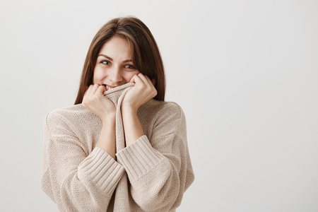Girl is blushing from receiving romantic confession. Cute adult brunette pulling collar of sweater on face, smiling cheerfully, being in love with boyfriend who make proposal, standing over gray wall Stock Photo