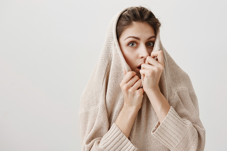 Curious woman wants to hear rest of scary story. Charming adult caucasian female pulling sweater on face and hiding it, peeking over collar with shocked expression, dropping jaw from surprise