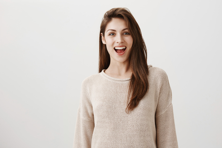 Say cheese and smile widely to camera. Portrait of pretty brunette european female in casual sweater, smiling broadly while saying hi, seeing familiar face on party, starting friendly conversation Stock Photo