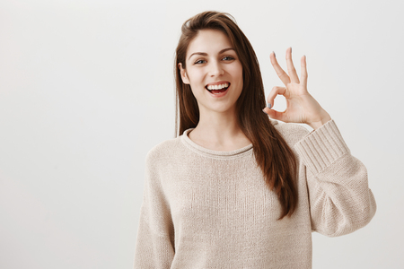 Woman will make sure everything will go fine. Portrait of friendly assured caucasian girl smiling positively raising hand near face, showing okay or great gesture, being confident in good result
