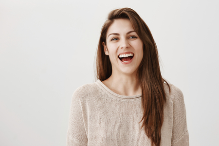Indoor portrait of attractive ordinary european woman with long brown hair laughing out loud while gazing at camera, being in great mood, chuckling over video in network, standing against gray wall