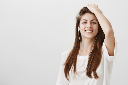 Boost of confidence with proper music list. Portrait of self-assured attractive girl touching hair and smiling broadly with raised chin, listening music in earphones, having great time over gray wall